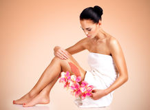 Beautiful young woman with flowers using a scrub. Royalty Free Stock Photos