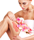 Beautiful young woman with flowers using a scrub. Stock Images