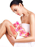 Beautiful young woman with flowers using a scrub. Royalty Free Stock Photo