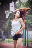 Beautiful young woman with fluttering hair playing basketball outdoors Stock Photography