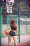 Beautiful young woman with fluttering hair playing basketball outdoors Royalty Free Stock Image