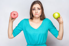 Beautiful young woman with freckles in green dress, confussed and trying to make choice between apple and donut. Royalty Free Stock Photos