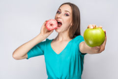 Beautiful young woman with freckles in green dress, eating pink donut and holding green apple. Studio shot on light gray background Stock Images