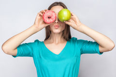Beautiful young woman with freckles in green dress, holding before her eyes green apple and pink donut and kissing. Stock Photo