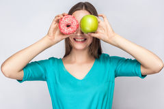 Beautiful young woman with freckles in green dress, holding before her eyes green apple and pink donut with toothy smile. Stock Photos