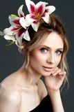 Beautiful young woman with fresh flowers in her hair looking down. Spring concept royalty free stock photography