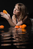 Beautiful young woman with fresh orange. Stock Images