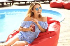 Beautiful young woman with fresh smoothie sitting on bean. Bag chair near swimming pool Stock Photo