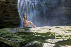 Beautiful young woman in front of waterfall - long exposure Stock Image