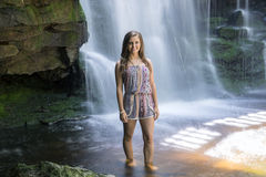 Beautiful young woman in front of waterfall - long exposure Stock Images