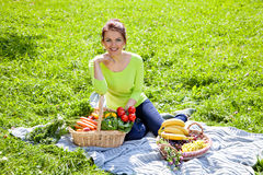 Beautiful young woman with fruits and vegetables at picnic Stock Photography
