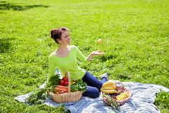 Beautiful young woman with fruits and vegetables at picnic on gr Royalty Free Stock Images