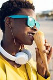 Beautiful young woman, funny and happy eating ice cream in the beach stock image