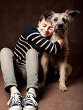 Beautiful young woman with a funny shaggy dog on a dark backgrou Stock Photography