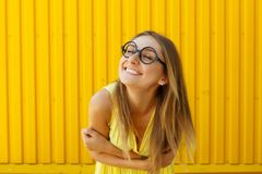 Beautiful young woman in funny toy glasses smiling over yellow b Stock Images