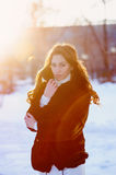 Beautiful young woman in a fur coat walks in the winter street Stock Images