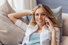 Beautiful young woman with gadget. Beautiful young woman in casual clothes is talking on the mobile phone, looking at camera and smiling, lying on sofa at home Stock Photography