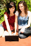 Beautiful young woman in the garden with laptop Royalty Free Stock Images
