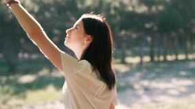 A young beautiful woman gently touches branches of a tree, covered with green and shining in the sunlight leaves. A beautiful young woman gently touches branches stock video footage