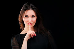 Beautiful young woman gesturing silence. Studio shot Royalty Free Stock Images