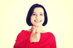 Beautiful young woman gesturing thumbs up. Stock Photo