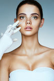 Beautiful young woman gets beauty injection in eye area from beautician. Royalty Free Stock Photos