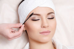 Beautiful young woman gets eyebrow correction procedure. Permanent makeup. Beautiful young woman gets eyebrow correction procedure. Young woman tweezing her Stock Images