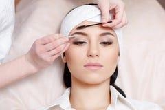 Beautiful young woman gets eyebrow correction procedure Stock Photography