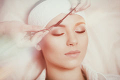 Beautiful young woman gets eyebrow correction procedure Stock Images