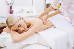 beautiful young woman getting back massage stock photos
