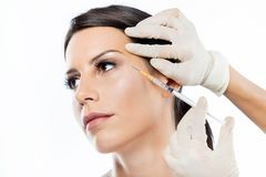 Beautiful young woman getting botox cosmetic injection in her face over white background. Portrait of beautiful young woman getting botox cosmetic injection in Stock Photos