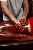 Beautiful young woman getting chocolate massage at spa Royalty Free Stock Photo