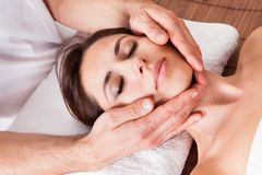 Beautiful young woman getting face massage Stock Image