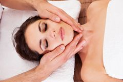 Beautiful young woman getting face massage Stock Photos
