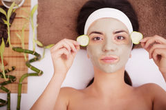 Beautiful young woman is getting facial clay mask at spa, lying with cucumbers on eyes Royalty Free Stock Image