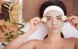 Beautiful young woman is getting facial clay mask at spa, lying with cucumbers on eyes Stock Images