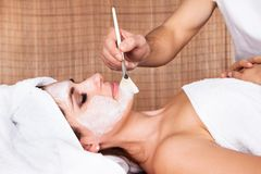 Beautiful young woman getting facial mask Stock Image