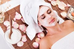 Beautiful young woman getting facial mask Royalty Free Stock Images