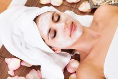 Beautiful young woman getting facial mask Royalty Free Stock Image