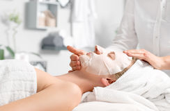 Beautiful young woman is getting facial mask at spa. Beauty treatment concept.  Woman is getting facial mask  at spa salon Royalty Free Stock Photography