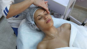Beautiful young woman getting facial massage with closed eyes in a spa salon stock video