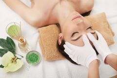 Beautiful young woman getting facial massage lying on the couch. Top view focused on the face stock images