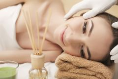 Beautiful young woman getting facial massage lying on the couch. Top view focused on the face stock image