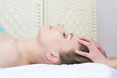Beautiful young woman getting facial massage in the spa salon, close-up portrait, side view