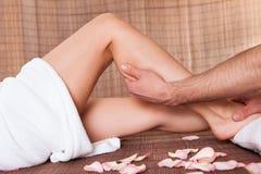 Beautiful young woman getting feet massage Stock Image
