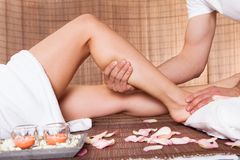 Beautiful young woman getting feet massage Stock Image