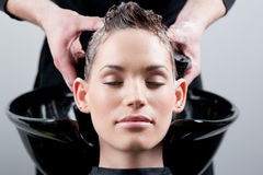 Beautiful young woman getting a hair wash Royalty Free Stock Photos