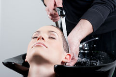 Beautiful young woman getting a hair wash Royalty Free Stock Photography