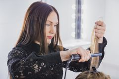 Beautiful young woman is getting her hair straightened at beauty saloon Stock Images