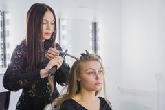 Beautiful young woman is getting her hair straightened at beauty saloon Stock Photos